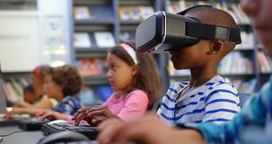 Side view of Caucasian schoolboy using virtual reality headset in the classroom 4k. Side view of Caucasian schoolboy using virtual reality headset in the stock video