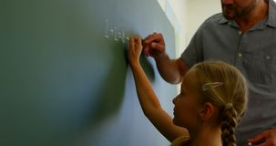Schoolgirl solving mathematical equation on chalkboard in classroom 4k. Side view of Caucasian schoolgirl solving mathematical equation on chalkboard in stock footage