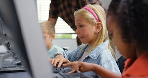 Side view of Caucasian schoolgirl studying on personal computer male teacher teaching schoolkids in. Male teacher teaching schoolkids on desktop pc in the stock video footage