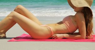 Side view of Caucasian woman in hat relaxing on the beach 4k. Side view of Caucasian woman in hat relaxing on the beach. Beautiful sea waves in the background 4k stock video footage