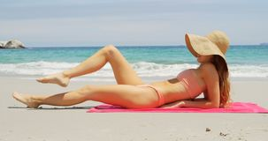 Side view of Caucasian woman in hat relaxing on the beach 4k. Side view of Caucasian woman relaxing in hat on the beach. Beautiful sea waves in the background 4k stock footage