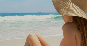 Side view of Caucasian woman in hat relaxing on the beach 4k. Side view of Caucasian woman in hat relaxing on the beach. She is smiling 4k stock footage