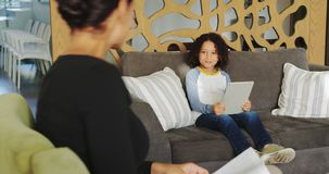 Side view of Caucasian woman reading magazine and African american boy using digital tablet on sofa stock footage