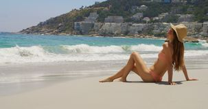 Side view of Caucasian woman relaxing on the beach 4k. Side view of Caucasian woman relaxing on the beach. She is looking at sea 4k stock video