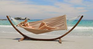 Side view of Caucasian woman relaxing in a hammock at beach 4k. Side view of Caucasian woman relaxing in a hammock at beach. Beautiful sky and calm sea in the stock video footage