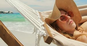 Side view of Caucasian woman relaxing in a hammock at beach 4k. Side view of Caucasian woman relaxing in a hammock at beach. She is asleep 4k stock footage