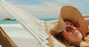 Side view of Caucasian woman relaxing in a hammock at beach 4k. Side view of Caucasian woman relaxing in a hammock at beach. She is asleep 4k stock video