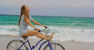 Side view of Caucasian woman riding a bicycle on the beach 4k. Side view of Caucasian woman riding a bicycle on the beach. She is having fun 4k stock video footage