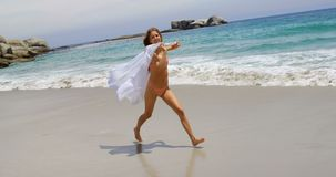 Side view of Caucasian woman running with sarong on the beach 4k. Side view of Caucasian woman running with sarong on the beach. She is having fun 4k stock video