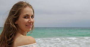 Side view of Caucasian woman smiling on the beach 4k. Side view of Caucasian woman smiling on the beach. She is looking at camera 4k stock footage
