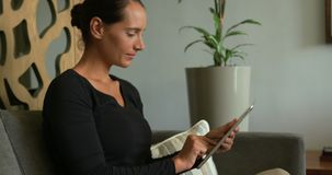 Side view of Caucasian woman using digital tablet in lobby at hospital 4k stock video footage
