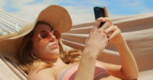 Side view of Caucasian woman using mobile phone in a hammock on the beach 4k. Side view of Caucasian woman using mobile phone in a hammock on the beach. She is stock footage
