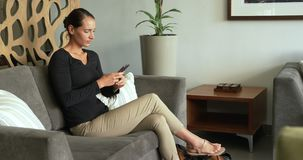 Side view of Caucasian woman using mobile phone on sofa in lobby at hospital 4k stock footage