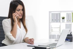 Side view of a centered businesswoman with brown hair is on her Stock Photography