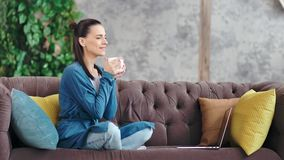 Charming domestic young female drinking coffee enjoying break on cozy couch at living room