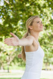 Side view of cheerful attractive woman doing yoga spreading her arms Stock Photography