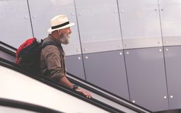 Outgoing grandfather standing on travelling staircase Stock Image