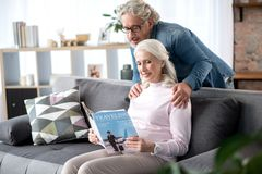 Happy senior man and woman entertaining with journal at home. Side view of cheerful elderly married couple are interested in news about traveling. They are royalty free stock images