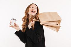 Side view of Cheerful elegant woman in coat holding packages. On shoulder and coffee in hand while looking back over grey background royalty free stock photos