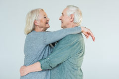 Side view of cheerful hugging senior couple Royalty Free Stock Photo
