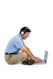 Side view of cheerful man listening music while using laptop Stock Photo