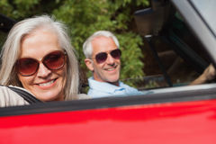 Side view of cheerful mature couple driving red cabriolet Royalty Free Stock Photography