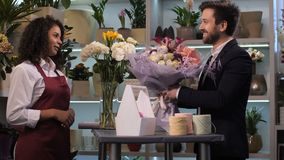 Happy florist giving floral arrangement to client. Side view of cheerful mixed race floral artist giving stylish flower composition to grateful customer with stock video