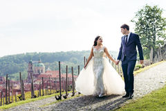Side view of the cheerful newlyweds holding hands while walking along the pavements at the background of the Prague Royalty Free Stock Photos
