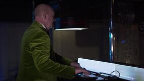 Side view of cheerful old Caucasian man mixing music on controller and waving to visitors in night club. Senior male DJ