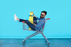 Side view of cheerful young man sitting in shopping cart Royalty Free Stock Images
