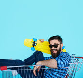 Side view of cheerful young man sitting in shopping cart Stock Photography
