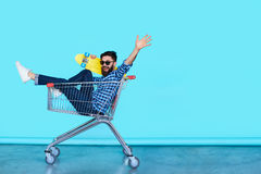 Side view of cheerful young man sitting in shopping cart. Carefree hipster fun. Side view of cheerful young man sitting in shopping cart with skateboard over Stock Photos