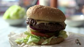 Side view of cheeseburger. Burger with sesame bun rotating. Fast food delivery stock video