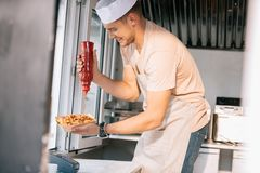 Side view of chef adding ketchup to hot dog. In food truck royalty free stock images