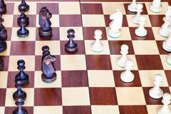 Side view of chess gameplay on chessboard close up. Side view of chess gameplay on wooden chessboard close up royalty free stock photography