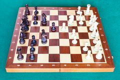 Side view of chess gameplay on wooden chessboard. On green baize table stock photo