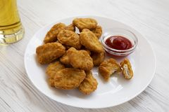 Side view, chicken nuggets with ketchup and glass of cold beer on a white wooden background. Close-up.  royalty free stock photos