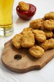 Side view, chicken nuggets with ketchup and glass of cold beer on a white wooden background. Closeup.  stock images