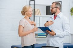 side view of chiropractic in white coat with notepad and smiling female patient