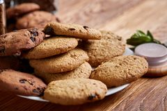 Side view of chocolate chip cookies on a wooden plate over rustic background, selective focus. Side view of chocolate chip cookies on a wooden plate over rustic Royalty Free Stock Photos