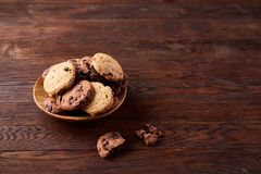 Side view of chocolate chip cookies on a wooden plate over rustic background, selective focus. Side view of chocolate chip cookies on a wooden plate over rustic Stock Image