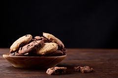 Side view of chocolate chip cookies on a wooden plate over rustic background, selective focus. Side view of chocolate chip cookies on a wooden plate over rustic Stock Photos