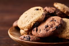Side view of chocolate chip cookies on a wooden plate over rustic background, selective focus. Side view of chocolate chip cookies on a wooden plate over rustic Royalty Free Stock Photo