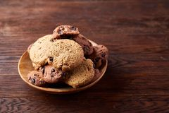 Side view of chocolate chip cookies on a wooden plate over rustic background, selective focus. Side view of chocolate chip cookies on a wooden plate over rustic Stock Photo
