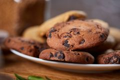 Side view of chocolate chip cookies on a wooden plate over rustic background, selective focus. Side view of chocolate chip cookies on a wooden plate over rustic Stock Photography