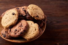 Side view of chocolate chip cookies on a wooden plate over rustic background, selective focus. Side view of chocolate chip cookies on a wooden plate over rustic Stock Images