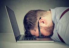 Overworked man lying on laptop. Side view of chubby man looking broken while lying on top of laptop Stock Photography