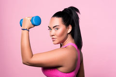 Side view of chubby mulatto woman holding dumbbell Royalty Free Stock Images