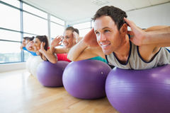 Side view of class exercising on fitness balls in a row Royalty Free Stock Image