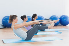 Side view of class stretching on mats at yoga class Royalty Free Stock Image